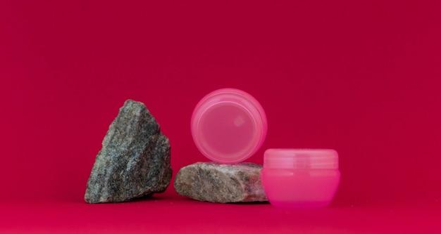 Un barattolo cosmetico si trova su una pietra, il secondo accanto su uno sfondo rosso