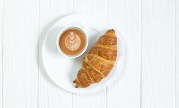 Un croissant e una tazza di caffè in schiuma d'arte sulla vista dall'alto del tavolo in legno bianco