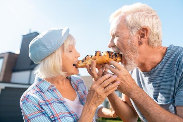 Un cornetto. coppia di pensionati amorevole sensazione divertente mangiare un croissant insieme fuori dalla loro casa