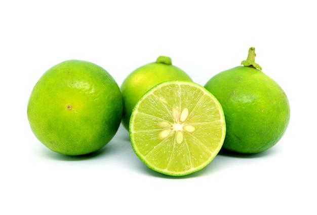 Una sezione trasversale limette fresche con i frutti interi su sfondo bianco