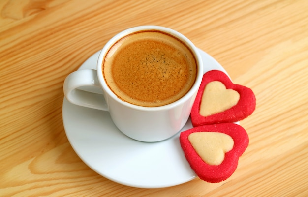 Una tazza di caffè espresso con un paio di biscotti a forma di cuore rosso sul tavolo di legno