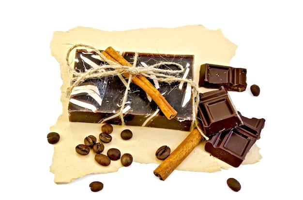 Un sapone scuro fatto in casa con spago, cannella, cioccolato e chicchi di caffè su carta gialla vecchia isolata su sfondo bianco