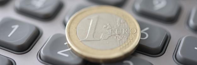Una moneta in euro è sul primo piano della calcolatrice