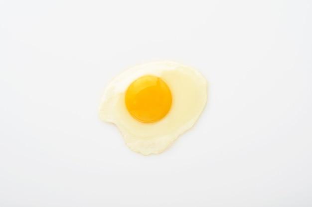 Un uovo fritto isolato su priorità bassa bianca con il percorso di residuo della potatura meccanica