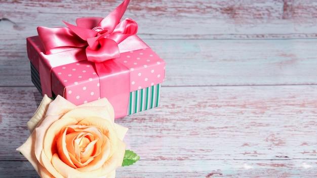 Una confezione regalo con un fiocco rosa su uno sfondo di legno, copia dello spazio di testo uno è aumentato nelle vicinanze.
