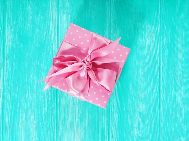 Una confezione regalo con un fiocco rosa su uno sfondo di legno, copia dello spazio del testo.