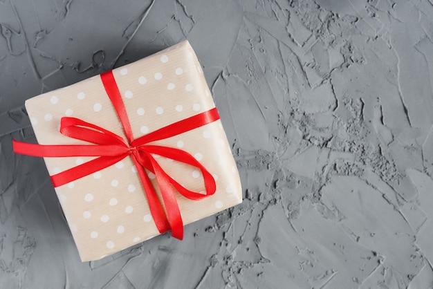 Una confezione regalo avvolta in carta artigianale a pois con nastro rosso su fondo in cemento