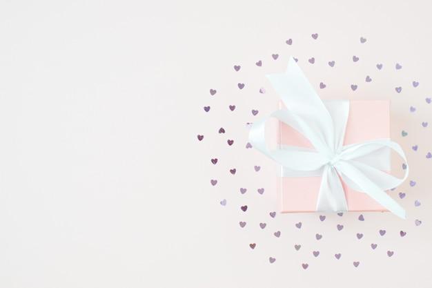 Un regalo su uno sfondo rosa intorno al cuore