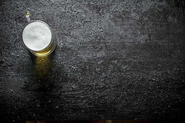 Un bicchiere di birra. su sfondo nero rustico