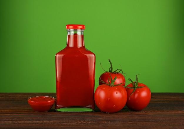 Una bottiglia di vetro di salsa ketchup e pomodori rossi freschi sul tavolo di legno wooden