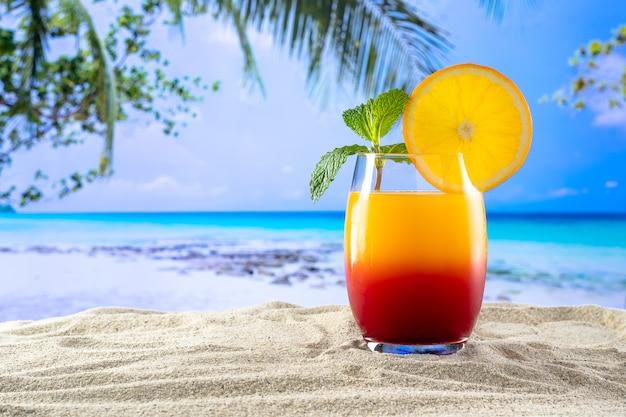 Un bicchiere con un drink sesso in spiaggia sulla sabbia e una spiaggia paradisiaca sullo sfondo