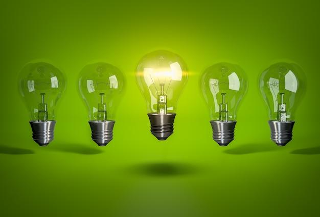 Una lampadina incandescente nella fila di lampadine su sfondo verde