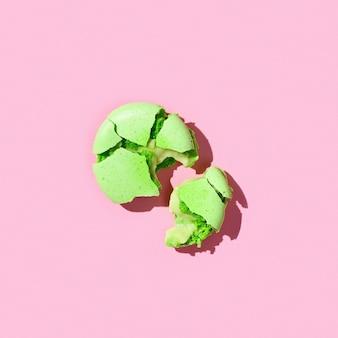 Un amaretto verde su sfondo colorato rosa macarons francesi colorati di biscotti