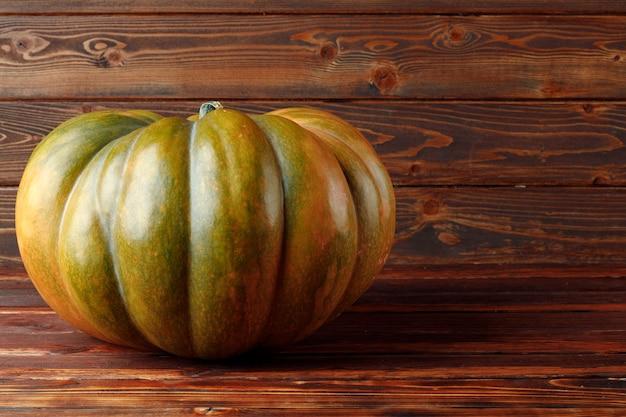 Una zucca verde su fondo di legno marrone