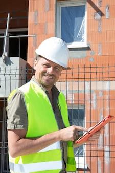 Un costruttore sorridente felice del responsabile del sito dell'ingegnere con il pc della compressa al cantiere di lavori stradali di geologia