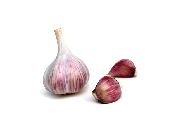 Una testa d'aglio, due chiodi di garofano su un piatto bianco.