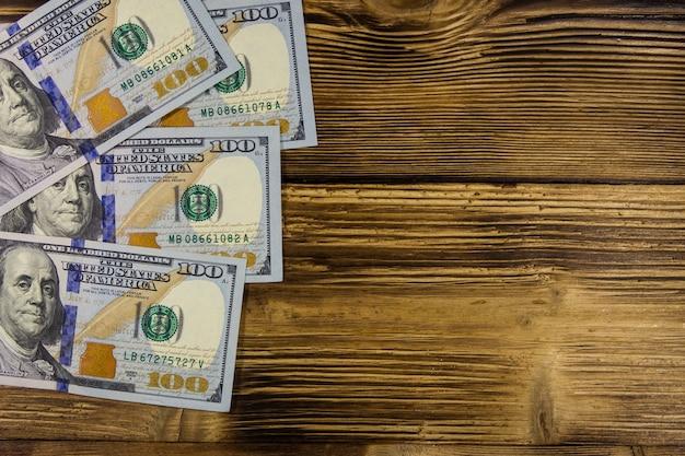 Banconote da cento dollari sulla scrivania in legno