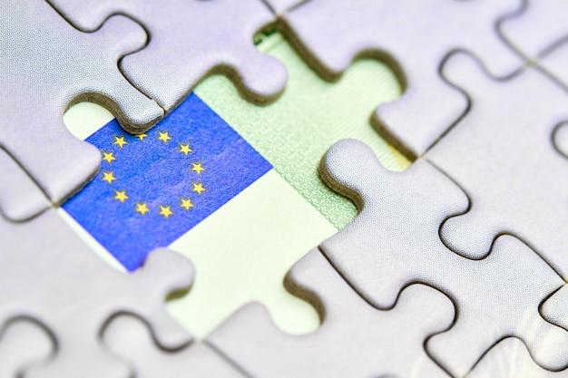 Banconota da cento euro e pezzi di un puzzle