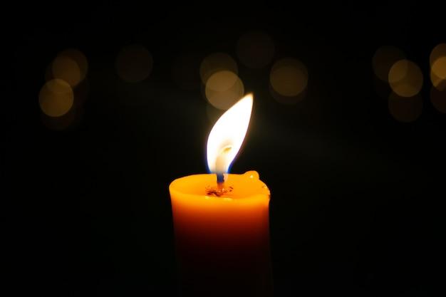 Una candela accesa che brucia vivacemente sullo sfondo nero