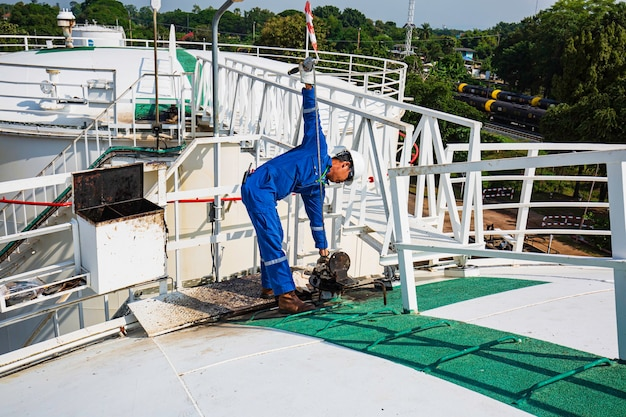 Un maschio ingegneri industriali livello di ispezione del serbatoio dell'olio combustibile in un impianto chimico