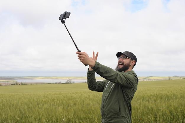 Un uomo che fa selfie con lo smartphone e mostra la pace all'aperto in campo, stile hipster con barba