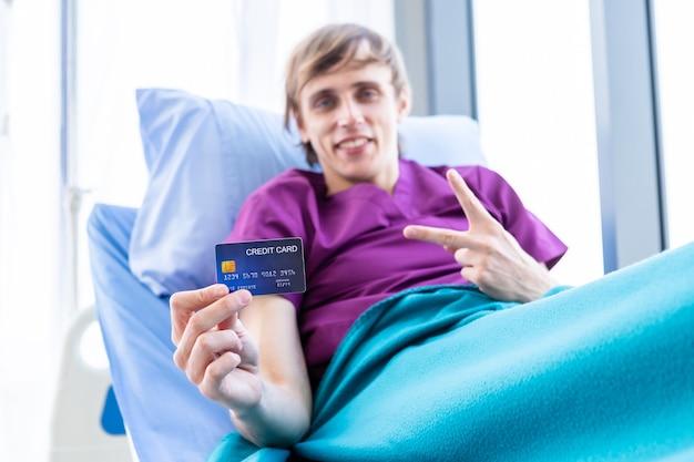 Un paziente uomo in mostra in possesso di una carta di credito sdraiata con solleva due dita in su combattendo sul letto nella stanza sfondo dell'ospedale, concetto di trattamento medico di pagamento