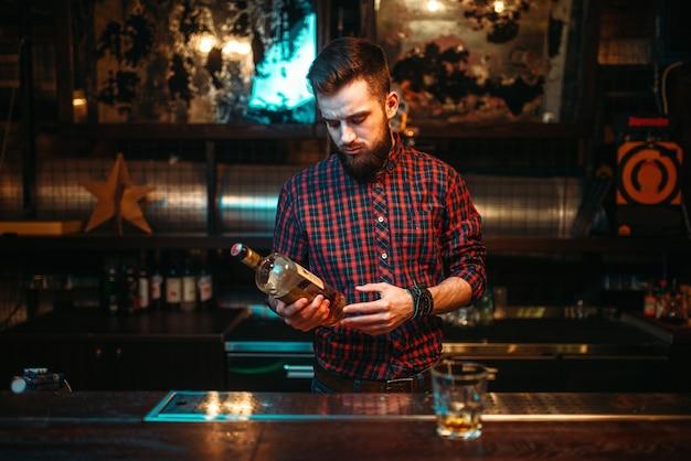 Un uomo con una bottiglia di bevanda alcolica in mano in piedi al bancone del bar. persona di sesso maschile in pub, alcolismo, ubriachezza