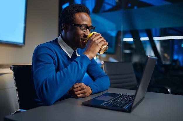 Un manager con gli occhiali lavora su un laptop nell'ufficio notturno