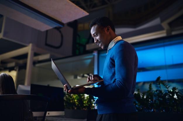 Un manager lavora su un laptop nell'ufficio notturno