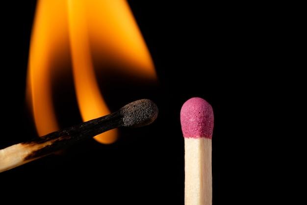 Un fiammifero acceso con una fiamma arancione accenderà l'altro