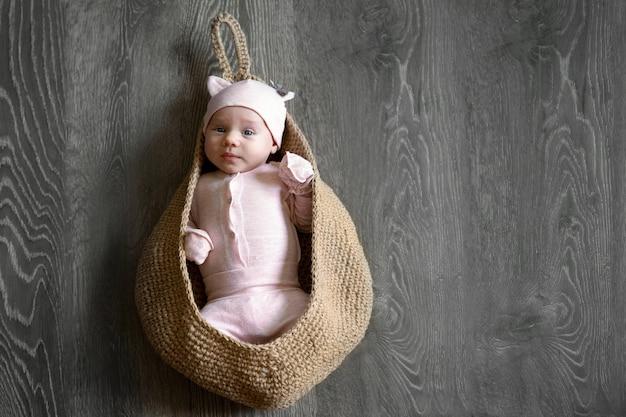 Bambino di un mese in una borsa lavorata a maglia, immagine di mock-up