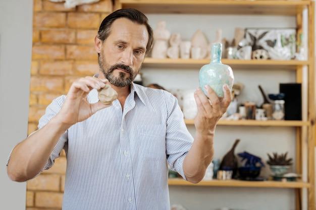 Ancora uno. artigiano creativo dai capelli scuri che guarda un bel vaso di ceramica mentre ne fa uno in più