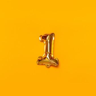 Un palloncino d'oro su uno sfondo giallo.