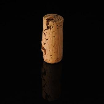 Un vecchio tappo di vino su sfondo nero con riflesso