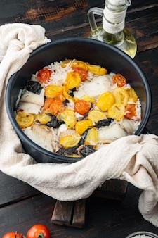 Un favoloso tegame di pesce, con riso basmati e pomodorini, su vecchio tavolo di legno wooden