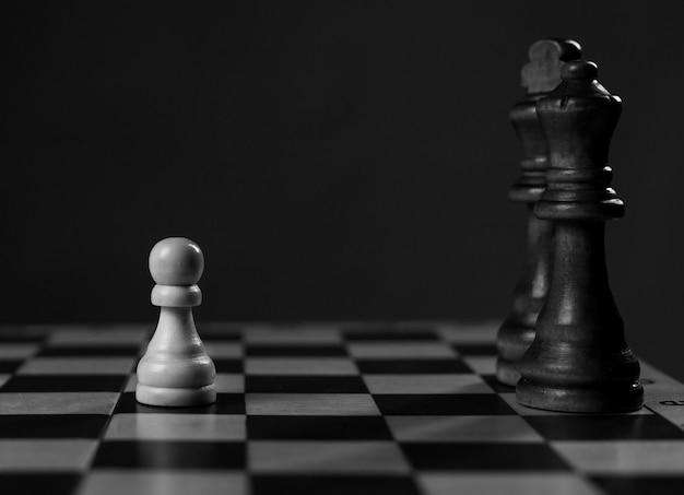 Una pedina prima del re e della regina sulla scacchiera, concetto.