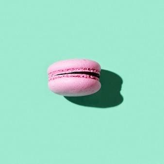 Un amaretto rosa su macaron biscotto verde luce dura