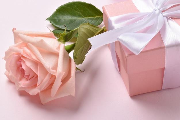 Una rosa rosa e una confezione regalo. minimalismo