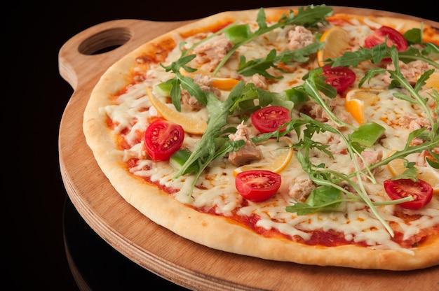 Una pizza su un vassoio di legno