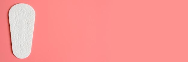 Un assorbente o tovagliolo mestruale quotidiano usa e getta da donna vuoto puro sul rosa.
