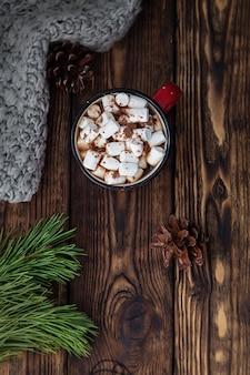 Una tazza rossa con bevanda calda con marshmallow e sciarpa lavorata a maglia sul natale in legno