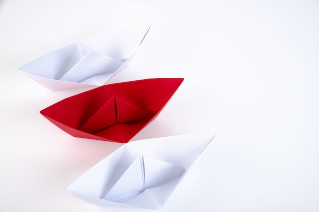 Una barchetta di carta rossa tra tante barchette di carta bianca