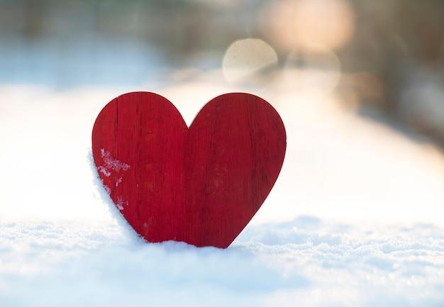 Un cuore di legno rosso con il bianco della neve in una giornata di sole