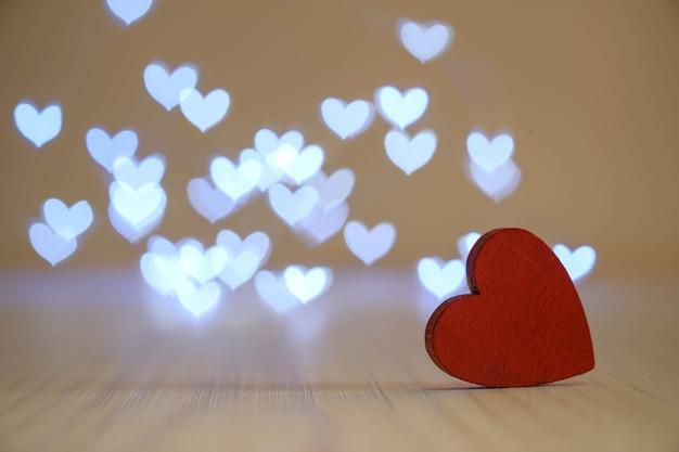 Un cuore di legno rosso su sfondo bokeh