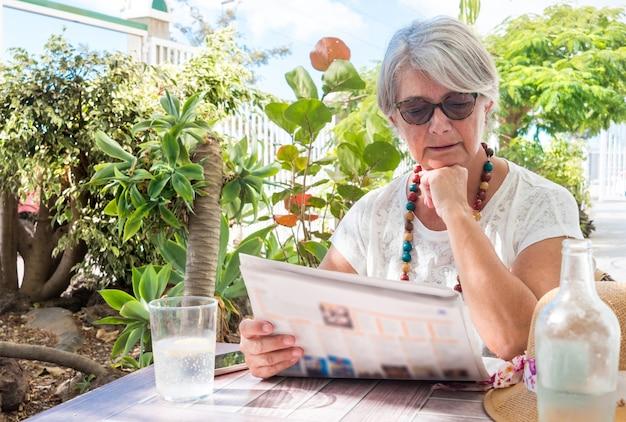 Una donna piuttosto anziana in pensione seduta e guardando il giornale in giardino. bere un bicchiere d'acqua. piante tropicali e cielo azzurro