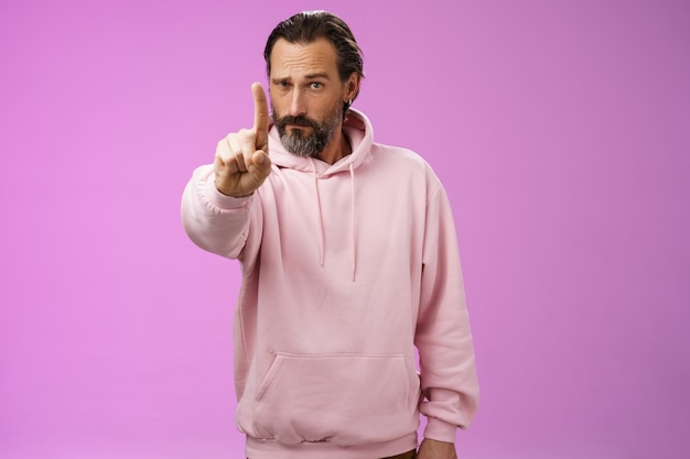 Una regola ascolta. il maschio barbuto adulto determinato e prepotente dall'aspetto serio in felpa con cappuccio rosa estende il dito indice primo numero che rimprovera la dichiarazione di vietare il cattivo comportamento, sfondo viola.