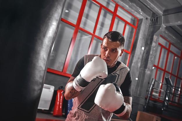 Un secondo prima di un atleta tatuato concentrato nella boxe di abbigliamento sportivo su un sacco da boxe pesante mentre