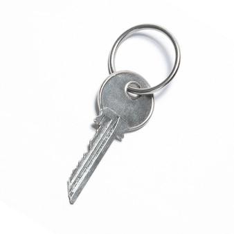 Una chiave d'argento isolata su priorità bassa bianca