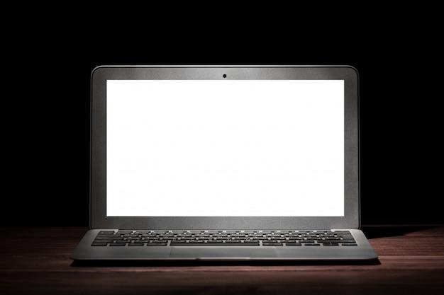 Un computer portatile moderno d'argento con lo schermo bianco vuoto sulla tavola di legno in una stanza scura su fondo nero.