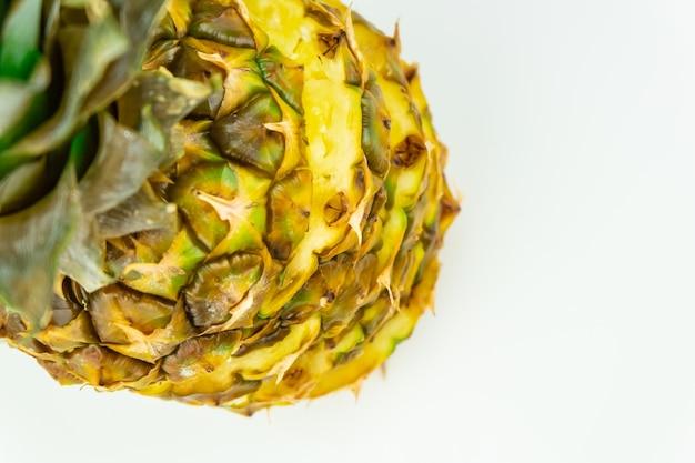 Un ananas a fette su sfondo bianco isolato, ripresa dall'alto. vista dall'alto di ananas fresco maturo in piedi sul tavolo bianco
